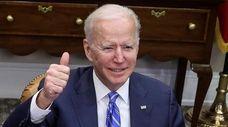 President Joe Biden gives a thumbs up as
