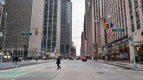 Pedestrians walk along 6th Avenue in Manhattan in