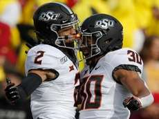 Oklahoma State wide receiver Tylan Wallace, left, celebrates