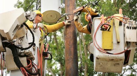 A PSEG Long Island crew transfers power lines