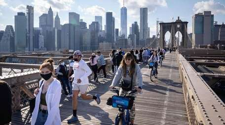 People walk and ride bicycles over the Brooklyn