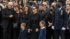 Irene Tsakos holds the hands of her children,