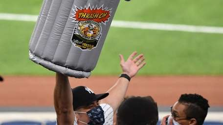 A fan holds an inflatable trash can during