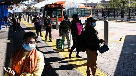 Passengers wearing protective masks prepared last month to