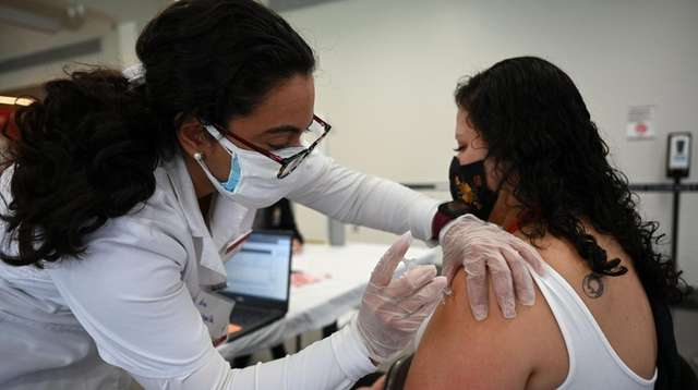 Molloy College nursing student Ana Quintanilla vaccinates Gabriela