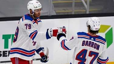 Rangers defenseman K'Andre Miller (79) is congratulated by