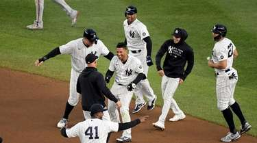 Yankees' Gleyber Torres, center, is congratulated by teammates