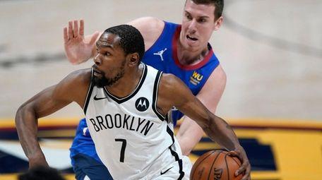 Nets forward Kevin Durant drives against Denver Nuggets