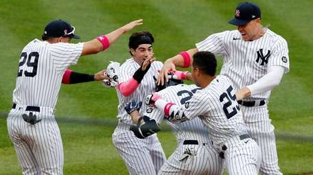 Giancarlo Stanton of the Yankees is mobbed by