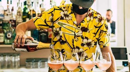 A bartender pours drinks while tending shop at
