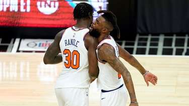 The Knicks' Reggie Bullock, right, bumps chests with