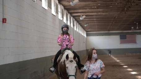 Eve Gross, 10, learns horseback riding at the