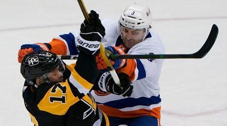 The Islanders' Adam Pelech checks the Penguins' Bryan