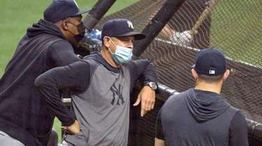 Yankees Manager Aaron Boone, center, watches batting practice