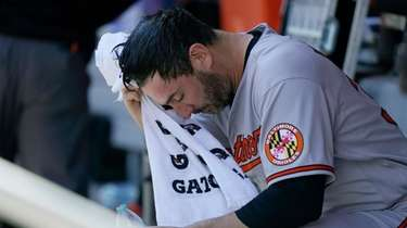 Orioles starting pitcher Matt Harvey wipes his face