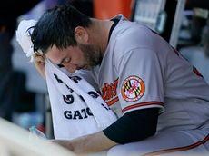 Orioles starting pitcher Matt Harvey wipes his face