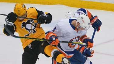 The puck slides under the Penguins' Colton Sceviour