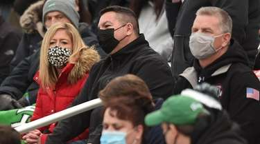 Spectators wear masks in the stands at a