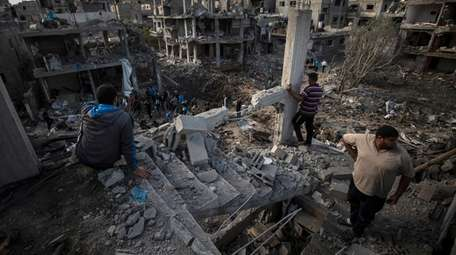 Palestinians inspect their destroyed houses following overnight Israeli