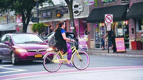 A woman bikes through downtown Patchogue