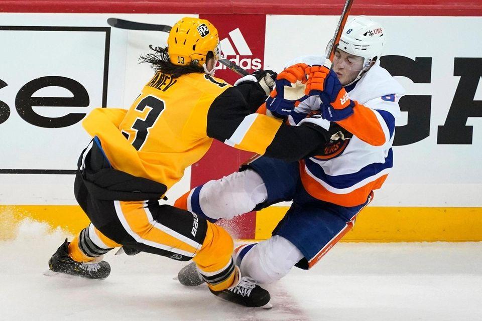 The Penguins' Brandon Tanev, left, checks the Islanders'