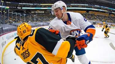 The Islanders' Scott Mayfield, right, checks the Penguins'
