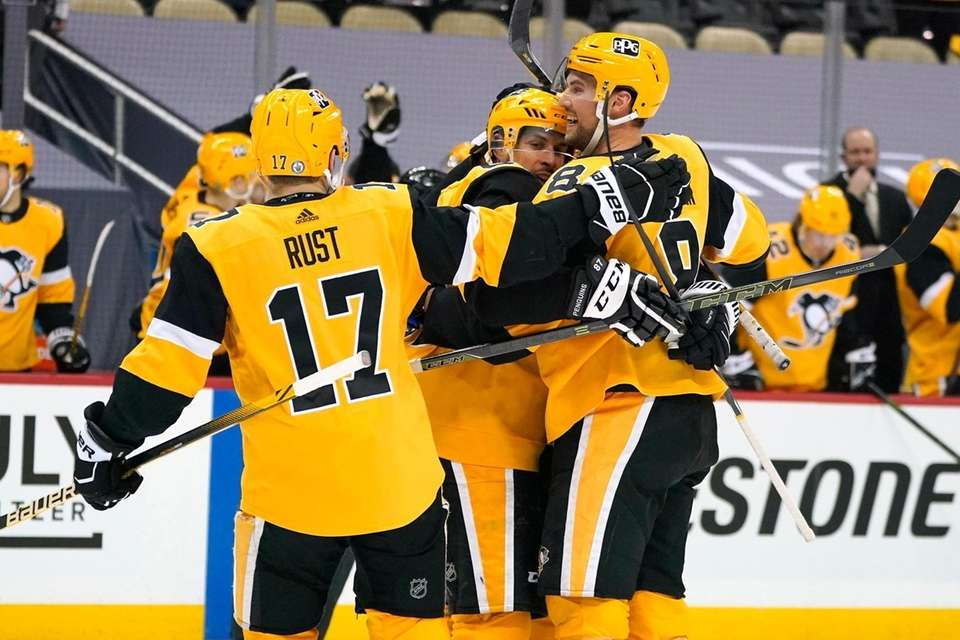 Pittsburgh Penguins' Sidney Crosby, center, is hugged by