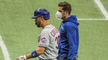 The Mets' Michael Conforto walks with a trainer