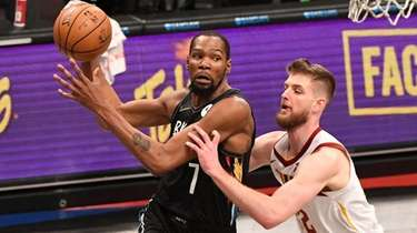 Nets forward Kevin Durant looks to pass defended