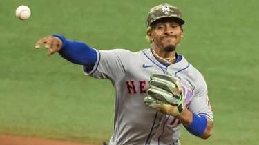 Mets shortstop Francisco Lindor, right, throws to first