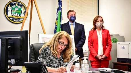 Riverhead Supervisor Yvette Aguiar signs paperwork to close