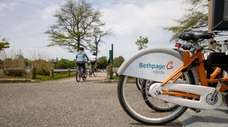 Bike riders pedal away Sunday near the Bethpage