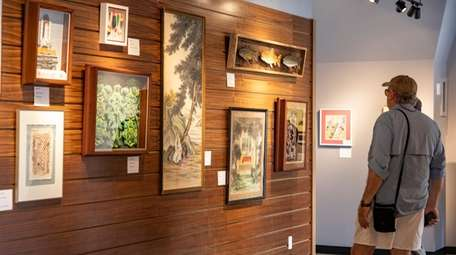 Visitors consider the art on display at the