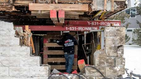 A contractor with Ironmen House Lifting works on