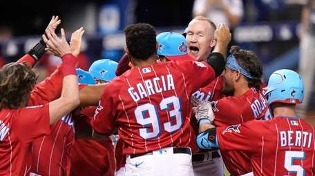 Miami Marlins' Garrett Cooper, right, is surrounded at