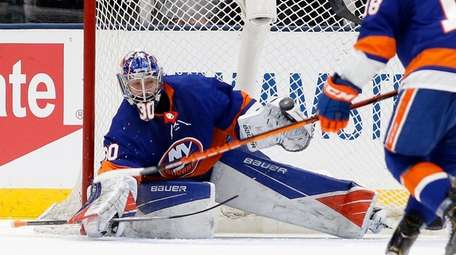 Ilya Sorokin #30 of the Islanders defends the