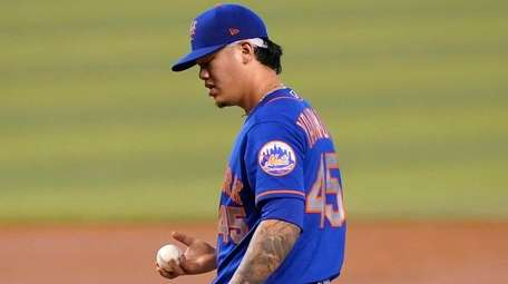 Mets starting pitcher Jordan Yamamoto stands on the