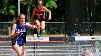 Runners compete in the novice 2000m steeple race,