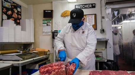 Butcher Enzo Tramontana slices meat at Farmingdale Meat