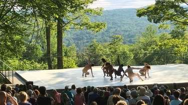 Dancers perform on an outdoor stage against a