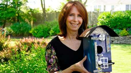 Jerry Abel's daughter, Shari, holds the tennis-themed birdhouse