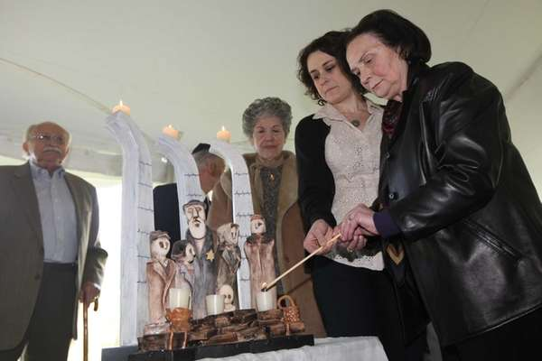 Jane Elias lights a candle with her mother,