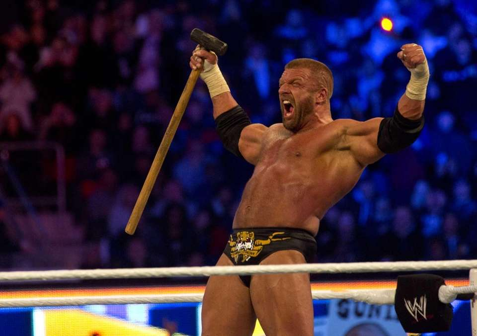 Triple H celebrates his victory against Brock Lesnar