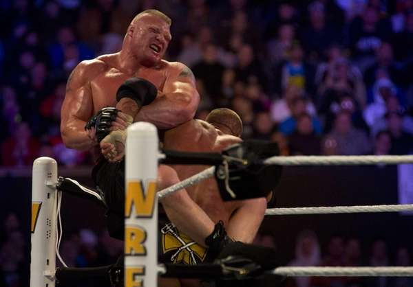 Triple H and Brock Lesnar wrestle during WrestleMania