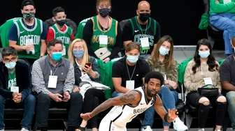 Fans watch as Brooklyn Nets guard Kyrie Irving