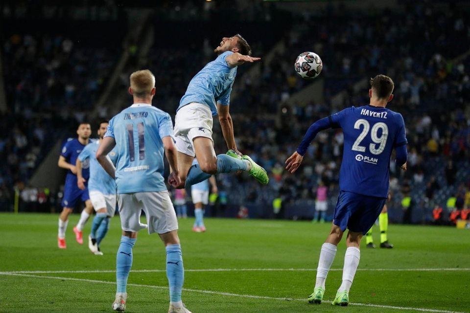 Manchester City's Ruben Dias, center, gestures as heads