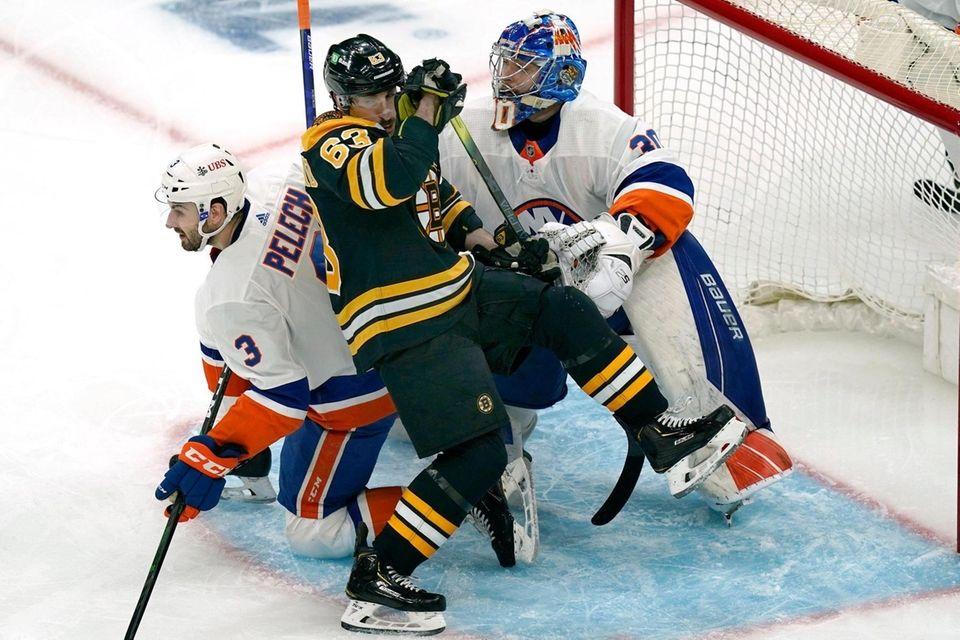 Bruins center Brad Marchand falls into Islanders defenseman