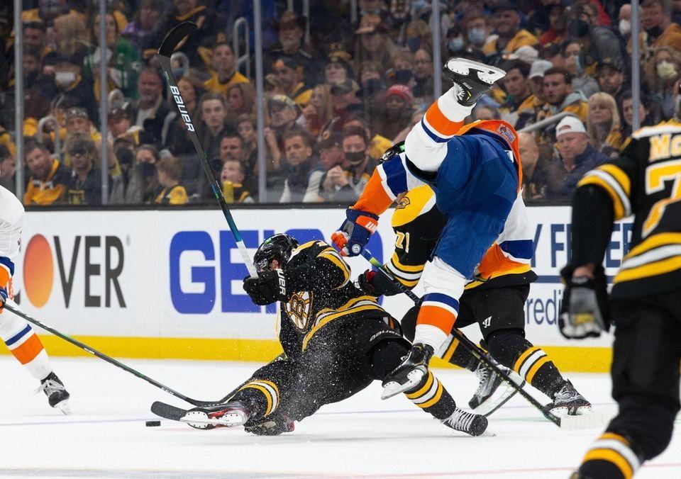 Craig Smith #12 of the Boston Bruins checks