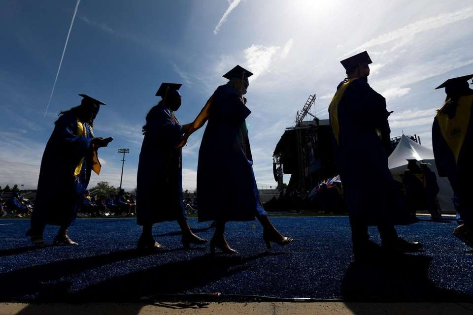 Graduates line up to cross the stage during