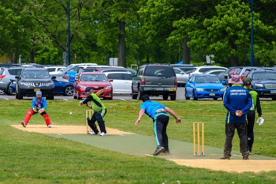 Men play cricket on the lawn at Eisenhower
